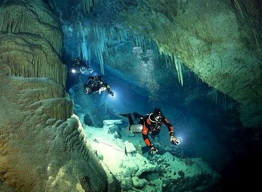 Three divers swim through the water-filled passages below the island of Bermuda