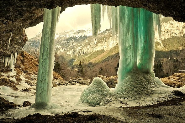 The frozen Fontana di Goriuda seen from behind, with the Julian Alps as a background, Italy